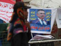 An anti-government protester passes a defaced picture of Adnan Al-Zurfi, Iraq's former prime minister-designate, in Baghdad in mid-March. (Hadi Mizban/AP)