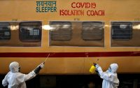 Workers disinfect a passenger train outside Kolkata, India, after it was converted into an isolation facility to deal with the coronavirus. (Rupak De Chowdhuri/Reuters)