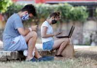 Dos jóvenes se conectan a internet desde un parque con wifi en La Habana, Cuba, el 21 de abril de 2020. (Yander Zamora/EPA-EFE/Shutterstock)