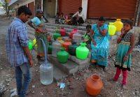 Residents use a public tap to fill their water containers in Hyderabad, India, last month. on March 18. (Mahesh Kumar A./AP)