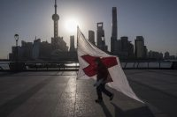 A man carries a kite with a red cross along the Bund as skyscrapers of the Pudong Lujiazui Financial District stand across the Huangpu River during sunrise in Shanghai on March 20. (Qilai Shen/Bloomberg) (Qilai Shen/Bloomberg News)