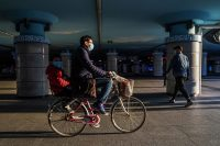 Lintao Zhang/Getty Images A Chinese man and a child wearing protective masks on a bike, Beijing, China, March 27, 2020