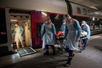 Thomas Samson/AFP via Getty Images Medical staff bringing a Covid-19 patient into a high-speed train at Paris's Gare d'Austerlitz station, heading for a hospital in Brittany, where cases of the pandemic have so far been limited, France, April 1, 2020