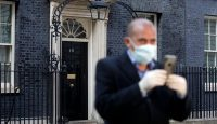 A member of the media wearing a protective face mask works in Downing Street where Britain's Prime Minister Boris Johnson is self-isolating in central London, 27 March 2020. Photo by TOLGA AKMEN/AFP via Getty Images.
