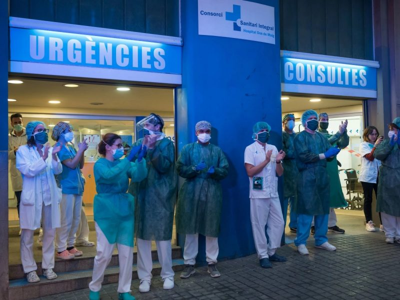Medical workers in Barcelona returning applause to residents who have applauded them. Health care professionals have denounced the failure of their authorities to protect them adequately.Credit Samuel Aranda for The New York Times