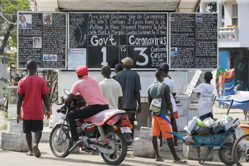 People look at a chalkboard in Monrovia, Liberia, giving updates on the coronavirus on Monday. (Ahmed Jallanzo/EPA-EFE/REX/Shutterstock)