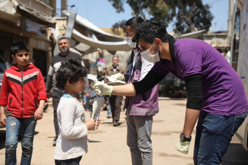 A member of a nongovernmental aid organization measures residents' temperatures as a preventive measure against covid-19 in Kafr Takharim, Syria, on Tuesday. (Ghaith Alsayed/AP)