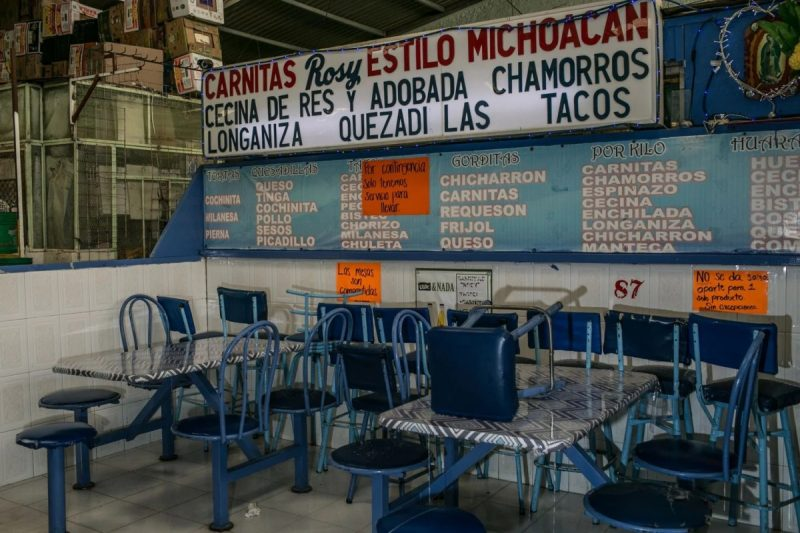 An empty taco stall in Mercado la Dalia in Mexico City. Signs advertise food to go. (Meghan Dhaliwal/FTWP)