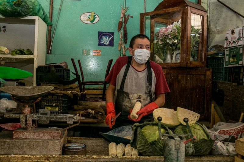 Javier Sánchez shaves corn off the cob at the stall he works at with his brother. (Meghan Dhaliwal/FTWP)