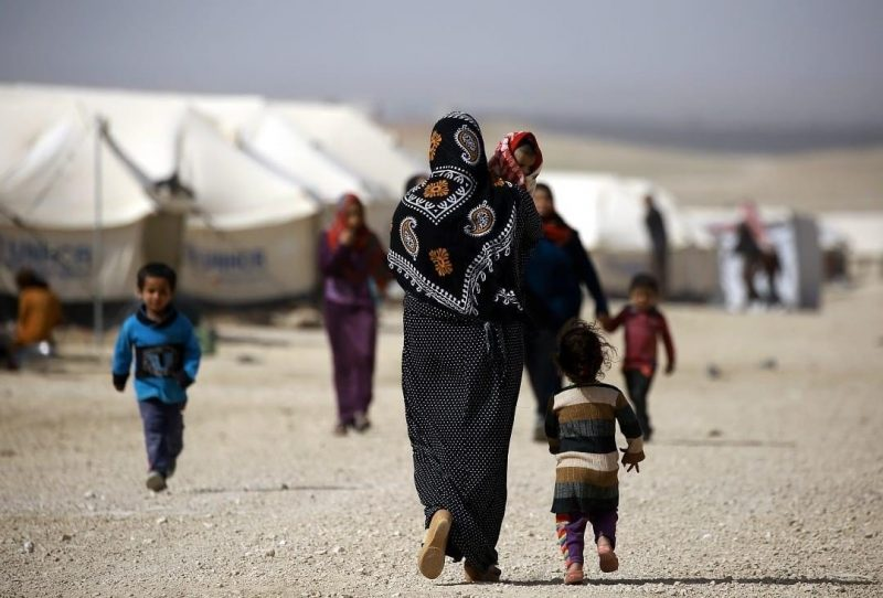 An Iraqi refugee carries her child as she walks around in a camp in al-Hol, Syria, 13 March 2017. AFP/DELIL SOULEIMAN