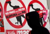 "A pedestrian walks past posters on the street that read ""No to the payment of the debt. Break with the IMF,"" in Buenos Aires on Wednesday. (Agustin Marcarian/Reuters)"