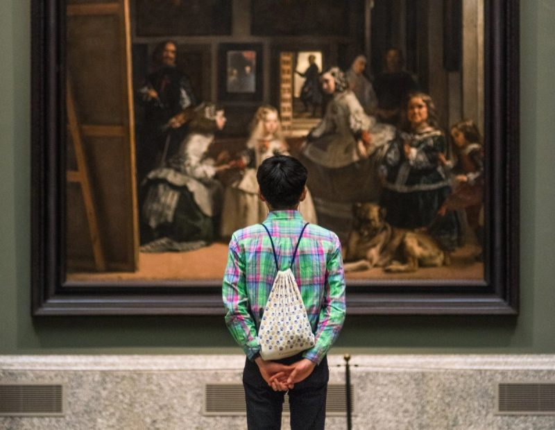 "A museumgoer contemplates ""​Las Meninas​,"" by Diego Velázquez, at the Prado in Madrid. Credit Emilio Parra Doiztua for The New York Times"