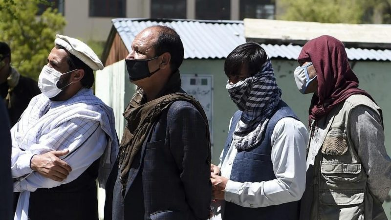 Men wearing facemasks queue up to receive free wheat from the government emergency committee in Kabul, 21 April 2020. AFP/Wakil Kohsar