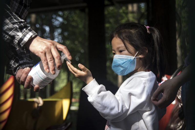 An employee gives out hand sanitizer to a girl in Zhongshan Park on Tuesday in Wuhan, China. (Getty Images)