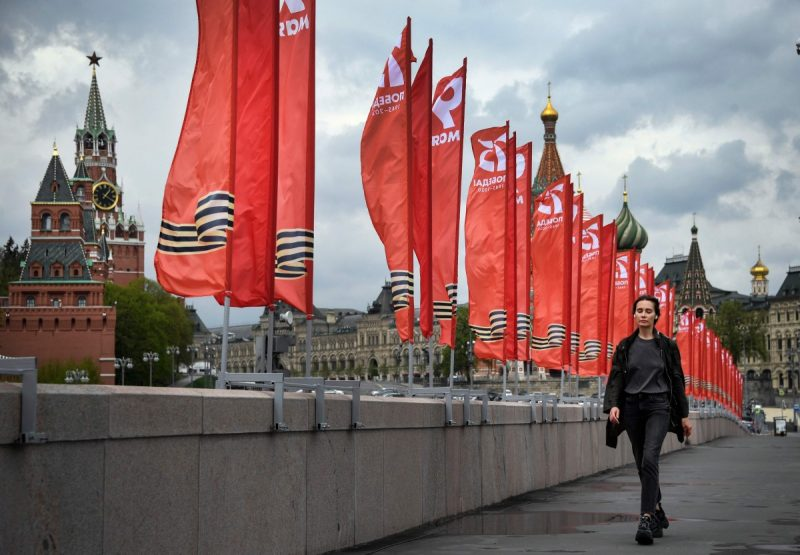 A woman walks past red banners devoted to Victory Day in downtown Moscow on Wednesday. (Alexander Nemenov/AFP via Getty Images)