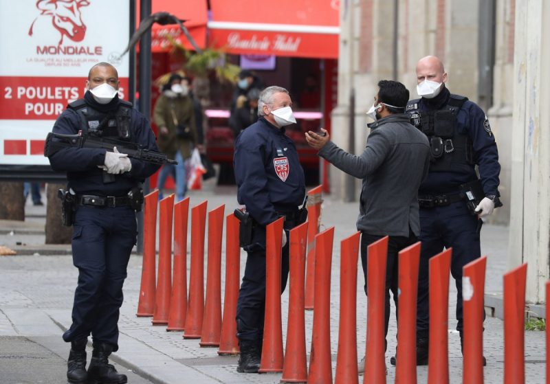 French police officers speak with a pedestrian in Saint-Ouen, near Paris, on April 2. (Ludovic Marin/Afp Via Getty Images)
