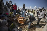 A man uses a hammer to remove pieces of a coffin to make it fit inside the grave during the burial of a person killed during a month of demonstrations aimed at ousting Haitian President Jovenel Moise, at a cemetery in central Port-au-Prince, Haiti, Oct. 16, 2019. The image was part of a series of photographs by Associated Press photographers which was named a finalist for the 2020 Pulitzer Prize for Breaking News Photography. (AP Photo/Rebecca Blackwell)