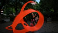 Performing a ribbon dance in Hankou Park, Wuhan on the same day as China warns its huge economy will suffer an immense hit from coronavirus. Photo by HECTOR RETAMAL/AFP via Getty Images.