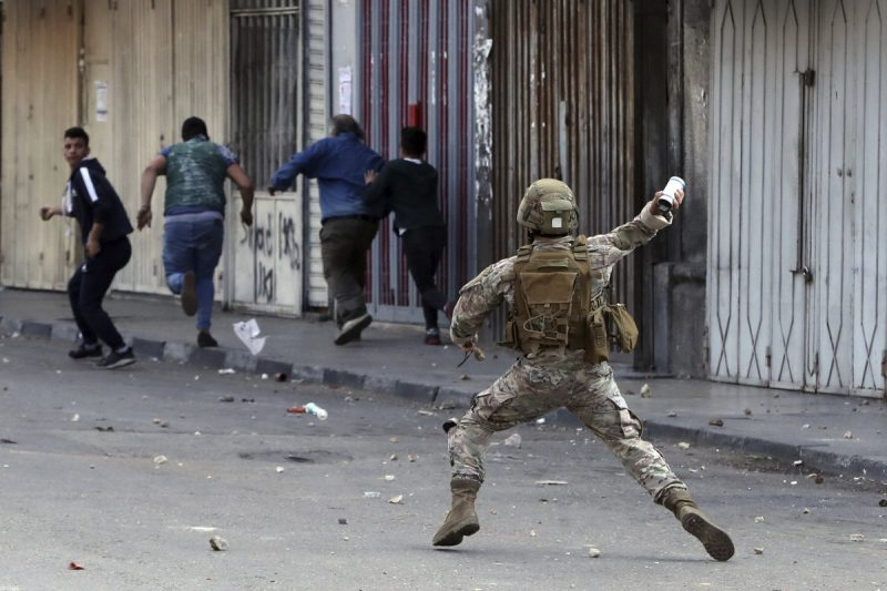 A Lebanese army soldier throws a tear-gas canister toward anti-government protesters in the northern city of Tripoli, Lebanon, on Tuesday. (Bilal Hussein/AP)