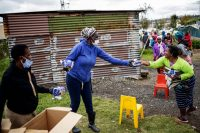 Local volunteers hand out bread to residents of the Booysens informal settlement during a bread distribution organized by a grass-roots organization in Johannesburg. (Michele Spatari/AFP/Getty Images)