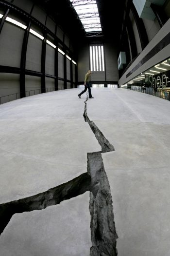 """Doris Salcedo's """"Shibboleth,"""" a temporary installation in the form of a crack running through the floor of the Tate Modern museum in central London in 2007. It represented segregation and racial hatred directed at immigrants and migrants. Credit Edmond Terakopian/Agence France-Presse — Getty Images"""