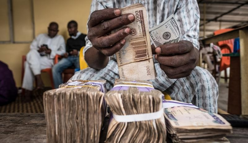 A currency dealer counts bundles of naira banknotes for exchange on the 'black market' in Lagos, Nigeria. Photographer: Tom Saater/Bloomberg via Getty Images.