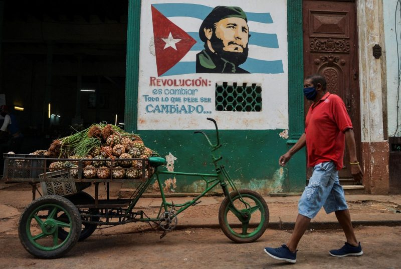 Yamil Lage/AFP via Getty Images A man wearing a face mask walks by a mural depicting Fidel Castro in Havana, Cuba, May 13, 2020