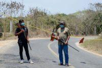 Habitantes y miembros de grupos de autodefensa resguardan la entrada a la playa en Marquelia, Guerrero,el 14 de abril de 2020, para evitar que entren turistas en la cotingencia por COVID-19 . (Francisco Robles / AFP )