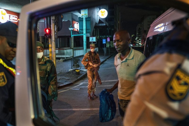 South African Defense Forces and police check a minibus driver who violated the lockdown in Johannesburg, on March 27. (Jerome Delay)