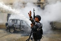 A police officer gestures to firefighters as they extinguish a police car that was set on fire by antigovernment protesters in Tripoli, Lebanon, on April 28. (Bilal Hussein/AP)
