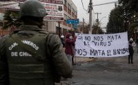 "A policeman looks at people holding a sign reading ""If the virus does not kill us, hunger will,"" in the La Pintana commune of Santiago, Chile, on Wednesday. (Martin Bernetti/AFP/Getty Images)"