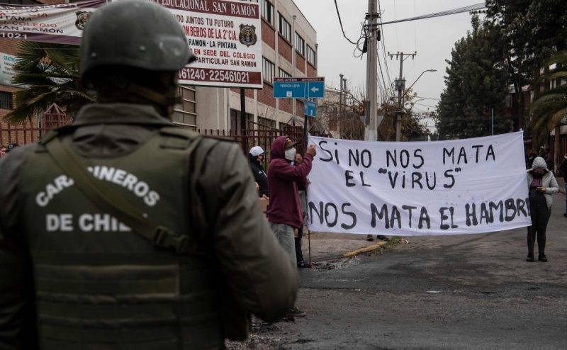 """A policeman looks at people holding a sign reading """"If the virus does not kill us, hunger will,"""" in the La Pintana commune of Santiago, Chile, on Wednesday. (Martin Bernetti/AFP/Getty Images)"""