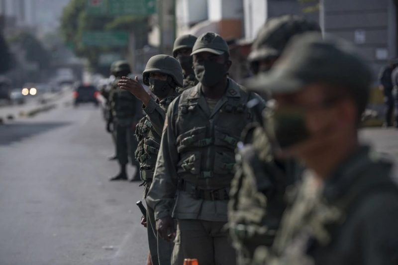 Members of the Bolivarian National Guard stand guard outside a gas station in Caracas, Venezuela, on April 6. (Carlos Becerra/Bloomberg)