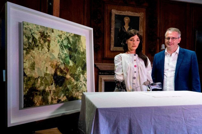 Ai-Da, a humanoid robot, and Aidan Meller, her inventor, present an oil painting in Oxford, England, created by artists based on a sketch by the robot. Credit Niklas Halle'n/Agence France-Presse — Getty Images
