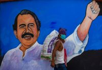A homeless man wears a face mask as he walks past a mural depicting Nicaraguan President Daniel Ortega in Managua on April 9. (INTI OCON/AFP via Getty Images)