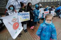 Ukrainians wearing protective face masks hold placards during a protest in front of the Cabinet of Ministers building in central Kyiv on Tuesday. (Sergey Dolzhenko/EPA-EFE/Shutterstock)
