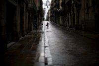 Un hombre camina por una calle vacía durante la cuarentena en Barcelona. Credit Emilio Morenatti/Associated Press
