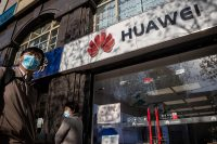 Pedestrians wearing face masks walk past a Huawei store on a Beijing street last month. (Nicolas Asfouri/AFP/Getty Images)
