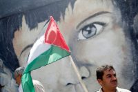 A demonstrator holding a Palestinian flag stands in front of a mural during a protest against Israel's plan to annex parts of the occupied West Bank, in Gaza City on Monday. (Mohammed Salem/Reuters)
