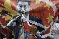 A banner featuring Chinese President Xi Jinping is torn during a protest against China in Ahmedabad, India, on Wednesday. (Ajit Solanki/AP)