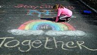 Girl makes chalk drawings on the driveway of her home to help brighten the mood of people passing by during the coronavirus pandemic. Photo by Thomas A. Ferrara/Newsday RM via Getty Images.