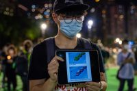 Alda Tsang/SOPA Images/LightRocket via Getty Images A participant displaying images on a tablet device at a vigil in Victoria Park linking pro-democracy protests with the 1989 Tiananmen Square in China, Hong Kong, June 4, 2020