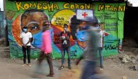 Grafitti artists from Mathare Roots Youth Organisation with their mural helping curb the spread of coronavirus in Nairobi, Kenya. Photo by TONY KARUMBA/AFP via Getty Images