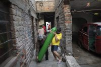 César García y un vecino cargan un cilindro de oxígeno a la casa de su hijastro en Lima, Perú, el 11 de junio de 2020. (Rodrigo Abd/AP Photo)