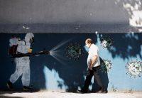 Un hombre camina por un mural en una calle de Río de Janeiro en junio. Credit Silvia Izquierdo/Associated Press