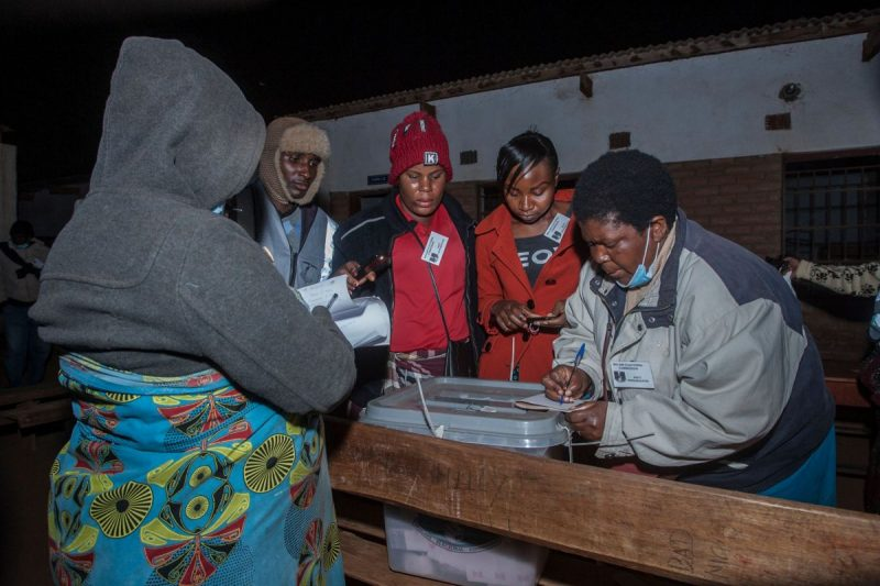 "Electoral officials and political party monitors close ballot boxes at the end of voting during Malawi's presidential election on Tuesday. Malawians returned to the polls for the second time in just over a year after the Constitutional Court in February ruled the May 2019 vote was fraught with ""grave and widespread irregularities."" (Amos Gumulira/AFP/Getty Images)"