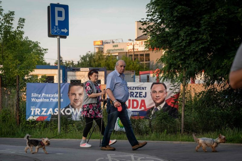 People walk their dogs as they pass campaign posters for Andrzej Duda, right, Poland's incumbent president and leader of the Law and Justice party; and opposition candidate Rafal Trzaskowski in a suburb of Warsaw on June 25. (Wojtek Radwanski/AFP/Getty Images)