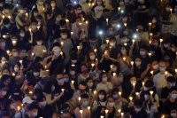 People hold candles as they gather to commemorate the 31st anniversary of the Tiananmen Square crackdown, in Hong Kong on Thursday, defying a unprecedented ban on congregating. (Roy Liu/Bloomberg News)