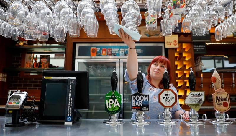 Cleaning glasses in preparation for pubs to reopen following an easing of coronavirus restrictions in England. Photo by TOLGA AKMEN/AFP via Getty Images.