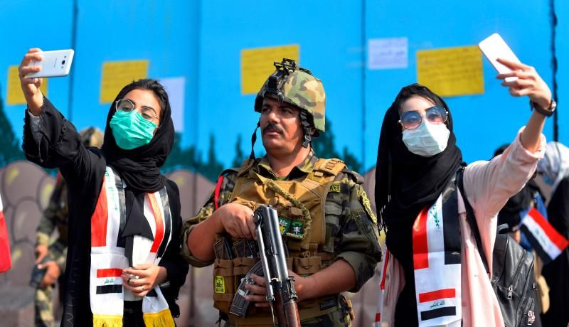 Iraqi students pose for selfies with a member of the security forces during anti-government protests in Diwaniyah. Photo by HAIDAR HAMDANI/AFP via Getty Images.